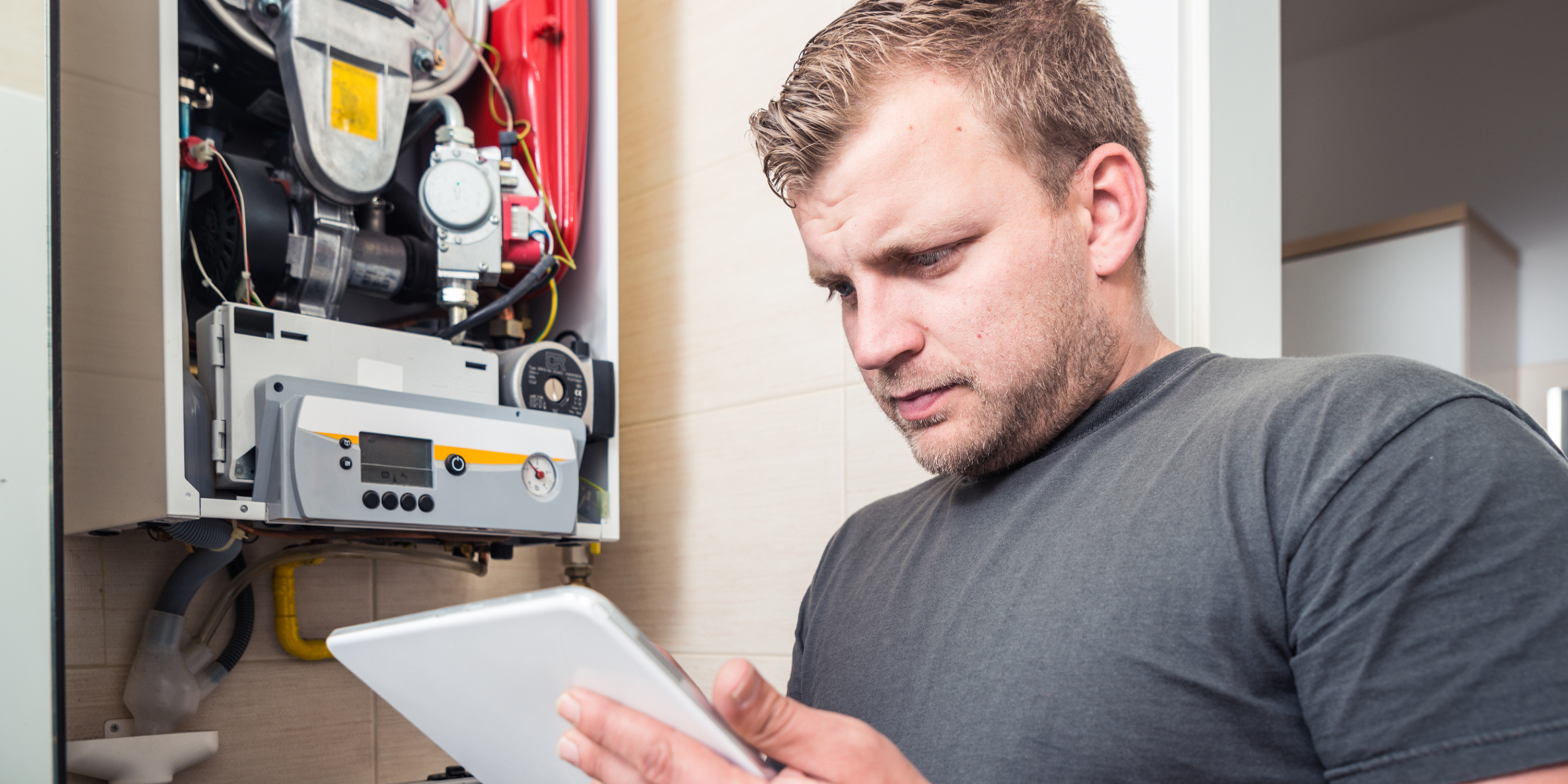 Worker checking iPad while repairing a boiler