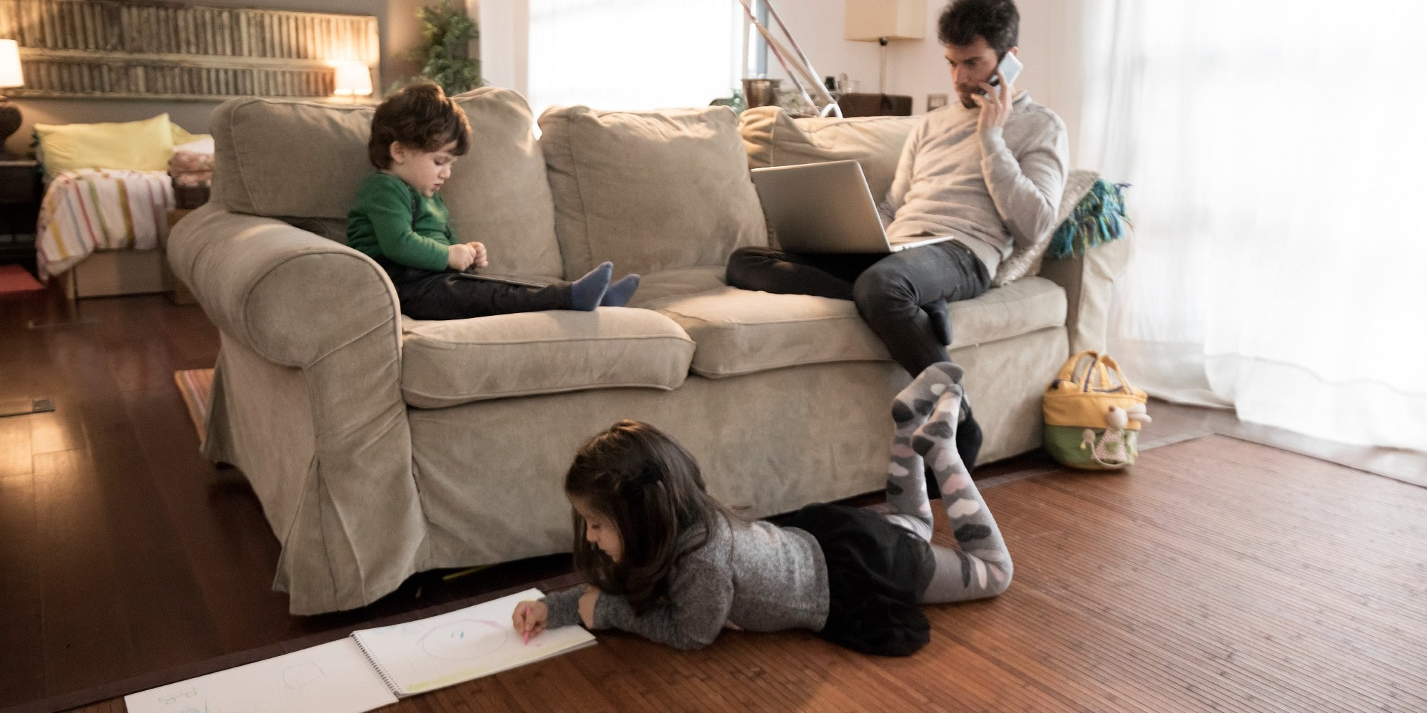 male father and two children sitting in in a living room working