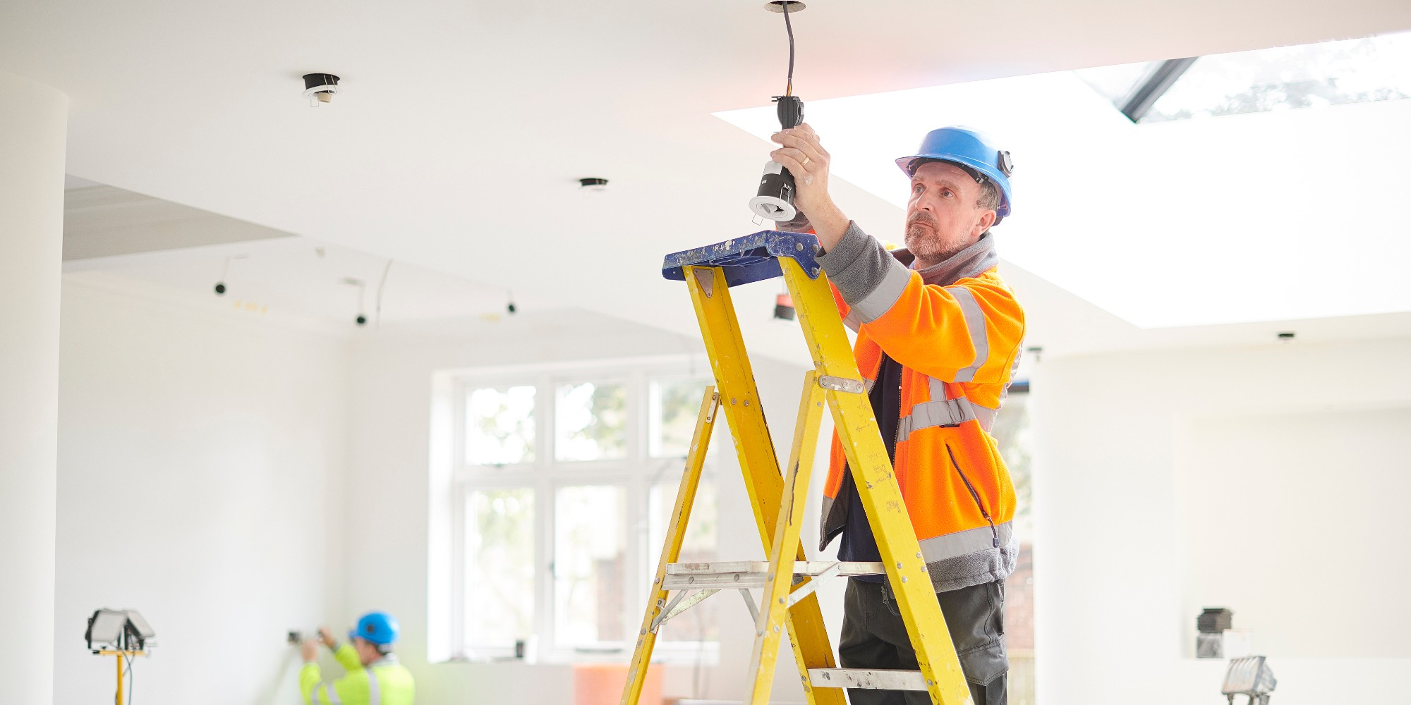 Electrician Installing Pot Light In Residential Home Standing On Ladder